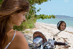 The girl on a motorcycle. The young girl rides a motorcycle on a wild beach Royalty Free Stock Photo