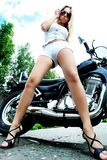 Girl with motorcycle. Shot of an attractive woman biker posing on her motorcycle Royalty Free Stock Image