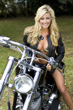 Girl On A Motorcycle. A beautiful young woman in a bikini and leather jackets sitting on a black and chrome motorbike