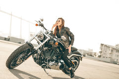 Girl on a motorcycle. She is beautiful, posing on a motorcycle at sunset stock photos