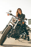 Girl on a motorcycle. She is beautiful, posing on a motorcycle at sunset royalty free stock photos