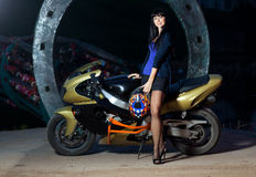 Girl and a motorcycle. Biker girl is standing next to a motorcycle at night. beautiful black-haired woman in a short skirt standing near a sportsbike. female Royalty Free Stock Image