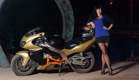 Girl and a motorcycle. Biker girl is standing next to a motorcycle at night. beautiful black-haired woman in a short skirt standing near a sportsbike. female Stock Image