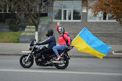 Girl on a motorcycle holding a flag of Ukraine Royalty Free Stock Images