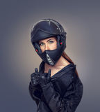 Girl motorcyclist in a black jacket and a helmet Royalty Free Stock Photography