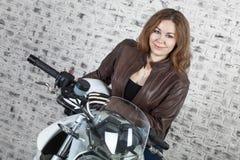 Girl motorcyclist in black jacket, helmet and gloves is in garage. Girl motorcyclist in a black jacket, helmet and gloves is in garage Royalty Free Stock Photo