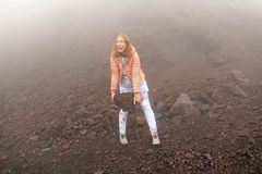 The girl on Mount Etna. The Etna volcano crater. Black Volcanic Earth, Volcanic Lava and Stones. Dense Fog on Mount Etna. Place royalty free stock photos
