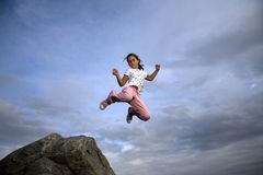 Girl on Mountain. A girl flies jumping off  the top of a mountain Royalty Free Stock Photography