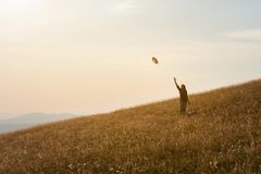 Girl in mountain having fun on huge idyllic field at sunset Royalty Free Stock Photo