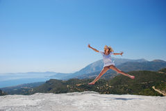 Girl on mountain jumping Stock Photo