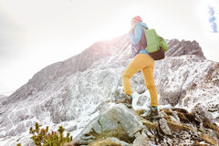 Girl on mountain ledge. Woman hiker with backpack on top of mountain stopped on sunny mountain ledge to catch breath after long hike Stock Photo