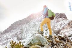 Girl on mountain ledge Stock Photo