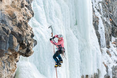 Girl mountaineer climbing a frozen waterfall and smiling Royalty Free Stock Image