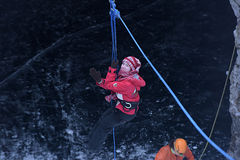 The girl in the mountaineering gear coming down on a rope Royalty Free Stock Image