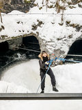 The girl in the mountaineering gear coming down on a rope to the Stock Image