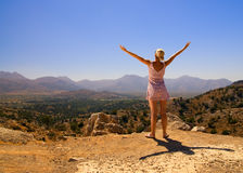 Girl in the mountains. Beautiful girl standing on a mountain with her hands wide open Royalty Free Stock Photography