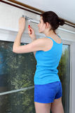 Girl mounts vertical blinds on wall, tighten red screwdri. Teen girl in a light blue singlet shirt and dark blue shorts, mounts vertical blinds on the wall stock image