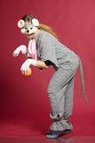 Girl in mouse costume. Beautiful girl in grey mouse costume with orange ball over red Stock Images