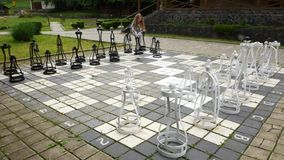 The girl moves big heavy metal chess pieces. Leisure in the open air.  stock footage