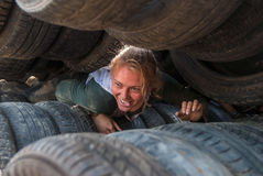 Girl moves between old tires. Tyumen Royalty Free Stock Photo