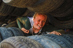 Girl moves between old tires. Tyumen. Tyumen, Russia - June 11, 2016: Race of Heroes project on the ground of the highest military and engineering school. Woman Royalty Free Stock Image