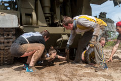 Girl moves under tank in extrim race by team help Stock Photo