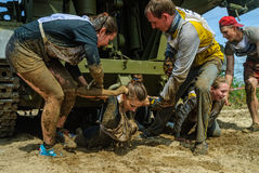 Girl moves under tank in extrim race by team help. Tyumen, Russia - June 11, 2016: Race of Heroes project on the ground of the highest military and engineering Stock Photo