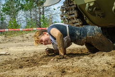 Girl moves under tank in extrim race. Tyumen Royalty Free Stock Image