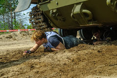 Girl moves under tank in extrim race. Tyumen Royalty Free Stock Photo