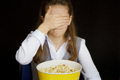 Girl in a movie theater. Closes her eyes Royalty Free Stock Photos