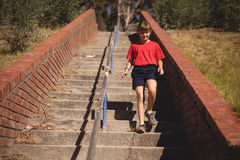 Girl moving down staircase during obstacle course. In boot camp royalty free stock images