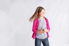Girl moving to music. Young girl moving her head to the music on her cell phone Stock Image