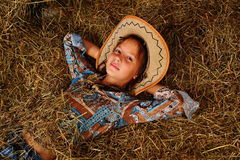 The girl on a mow. The little girl in a shed near to a butt, a photo in a retro style Stock Photos