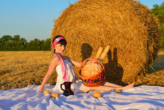 The girl on a mow with a basket of bread and a jug of milk Stock Photography