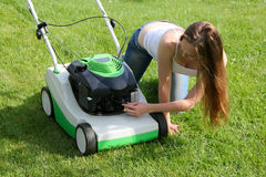 Girl and mower on the grass. Cute girl check the spark plug for lawnmowers Royalty Free Stock Photo