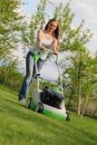 Girl mows the lawn. In the garden Royalty Free Stock Photos