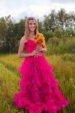 Girl muddy prom dress holding flowers. Girl muddy red prom dress holding bouquet flowers royalty free stock image