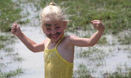 Girl in muddy water. Little girl playing in muddy water dirtying her clothes Royalty Free Stock Photography