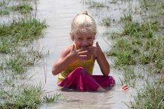 Girl in muddy water. Little girl playing in muddy water dirtying her clothes royalty free stock images