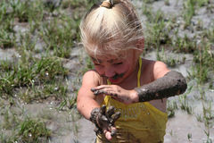 Girl in muddy water. Little girl playing in muddy water dirtying her clothes stock photos