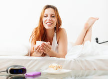 Girl with mug of cafe in her bed Royalty Free Stock Photos