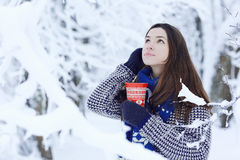 Girl with a mug of hot drink in winter forest Stock Photo