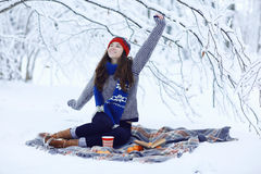 Girl with a mug of hot drink in winter forest Royalty Free Stock Images