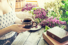 A girl with mug and lilac. Royalty Free Stock Image