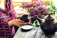 A girl with mug and lilac. Stock Image