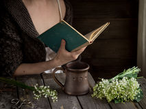 A girl with mug,white flowers and book. Royalty Free Stock Photography