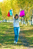 The girl with multi-colored packages going on park Stock Image