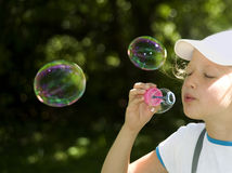Girl and  multi-colored  soap  bubbles Stock Photo