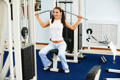 Girl on multi gym. Portrait of beautiful girl working out on multi gym Royalty Free Stock Images