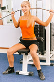 Girl on multi gym. Portrait of beautiful girl in orange vest working out on multi gym Royalty Free Stock Photography